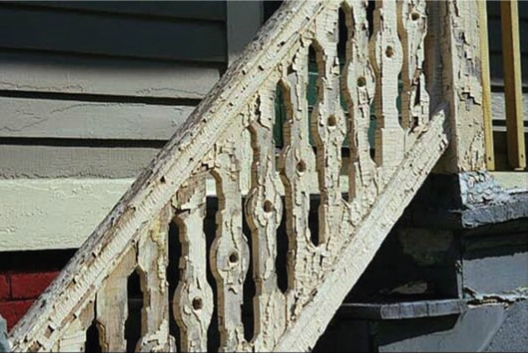 Outdoor Stairs To A House Featuring A Banister With Badly Peeling Paint