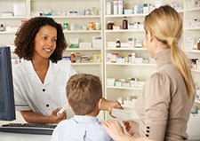 Pharmacist talking to mother and child